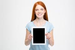 显示空白的片剂屏幕的红头发人妇女 免版税库存图片