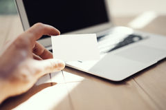 显示空白的白色名片和使用现代膝上型计算机木头表的照片人 被弄脏的背景 大模型准备好为 免版税库存图片