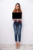显示空白的膝上型计算机屏幕的愉快的妇女 库存图片