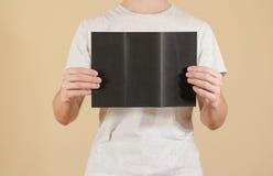 显示空白的黑飞行物小册子的人 详细的小册子 Leafle 免版税库存照片