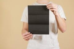 显示空白的黑飞行物小册子的人 详细的小册子 Leafle 库存图片
