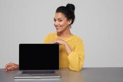 显示空白的黑comuter屏幕的愉快的妇女 免版税库存照片
