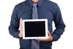显示空白的taplet个人计算机的愉快的微笑的年轻商人画象  免版税库存图片