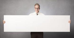 显示空白空的面板的微笑的生意人。 图库摄影