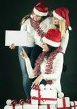 显示空白纸的圣诞老人服装的三个女孩 免版税图库摄影