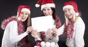 显示空白纸的圣诞老人服装的三个女孩 免版税库存图片