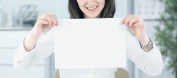 显示空白纸的女商人,坐在书桌后 免版税库存图片