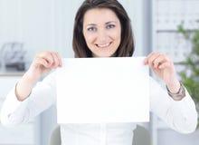 显示空白纸的女商人,坐在书桌后 免版税库存照片
