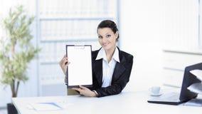 显示空白纸的行政女商人,坐在她的书桌 库存照片