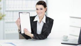 显示空白纸的行政女商人,坐在她的书桌 免版税库存图片