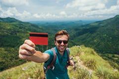 显示空的信用卡的年轻微笑的男性 他站立在山顶部并且显示室外秀丽 免版税库存照片