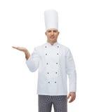 显示空的棕榈的愉快的男性厨师厨师 库存照片