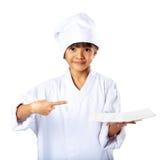 显示空的白色板材的小亚裔女孩厨师 免版税库存照片
