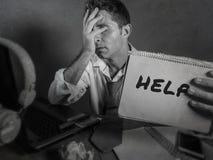 显示笔记薄的年轻杂乱和沮丧的商人请求帮忙绝望和哀伤在办公室看ov的便携式计算机书桌 库存图片
