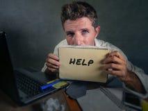 显示笔记薄的年轻杂乱和沮丧的商人请求帮忙绝望和哀伤在办公室看ov的便携式计算机书桌 免版税图库摄影
