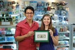 显示第一份美元收入的愉快的店主画象  免版税库存图片