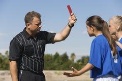 显示红牌的裁判员对女性足球运动员 图库摄影