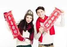 显示红色对联的亚洲夫妇 愉快的春节 免版税库存图片