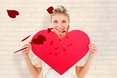显示红色心脏的可爱的年轻金发碧眼的女人的综合图象 免版税库存图片