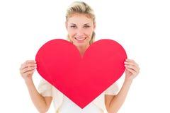显示红色心脏的可爱的年轻金发碧眼的女人 免版税库存照片