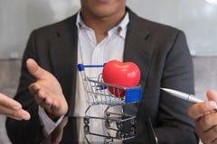 显示红色心脏的商人在数字式蓝色购物车 图库摄影