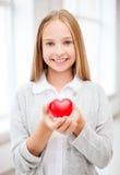显示红色心脏的美丽的十几岁的女孩 免版税库存照片