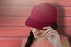 显示红色盖帽的微笑的女性模型的综合图象 免版税库存图片