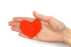 显示红色纸心脏的女性手作为爱的标志 免版税库存图片
