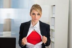 显示红色超级英雄服装的女实业家 免版税库存照片