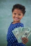 显示纸币的女孩画象对墙壁 图库摄影