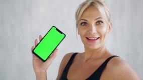 显示绿色屏幕手机,体育应用程序的微笑的适合的妇女 股票录像