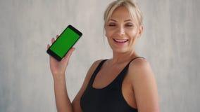 显示绿色屏幕手机,体育应用程序的微笑的适合的妇女 影视素材
