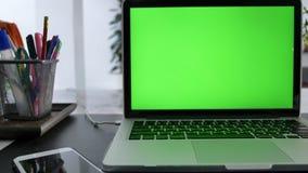 显示绿色色度关键屏幕的手提电脑在一张书桌上站立在客厅 移动式摄影车被射击的左到右 4K 股票视频