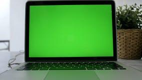 显示绿色色度关键屏幕的手提电脑在一张书桌上站立在客厅 移动式摄影车被射击的左到右 4K 股票录像