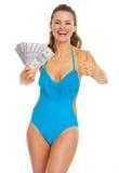 显示美元和赞许的爱好者泳装的微笑的妇女 库存图片