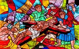 显示耶稣在十字架上钉死的彩色玻璃 库存图片