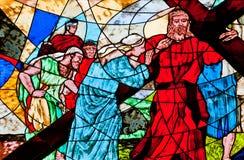 显示耶稣的彩色玻璃运载交叉 免版税库存图片