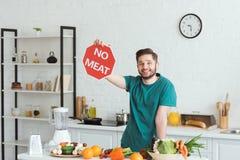 显示肉标志的英俊的素食主义者人 图库摄影