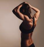 显示肌肉后面的健身女性 免版税库存图片