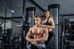 显示肌肉和锻炼的美好的年轻运动的夫妇在健身房在photoshooting期间 库存照片