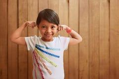 显示肌肉的亚裔小女孩 免版税图库摄影