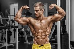 显示肌肉的健身房的性感的肌肉人 强的男性赤裸躯干吸收,解决 免版税库存照片
