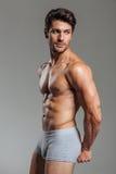 显示肌肉的性感的年轻深色的人 免版税图库摄影