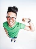 戴显示肌肉的行家眼镜的滑稽的英俊的人-广角 免版税库存照片