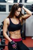 显示肌肉的运动少妇在锻炼以后在健身房 免版税图库摄影