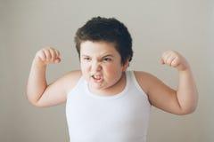 显示肌肉锻炼牙的儿童孩子 免版税图库摄影
