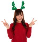 显示胜利标志的亚裔圣诞节女孩。 免版税库存图片