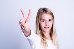 显示胜利标志的好白肤金发的女孩 库存图片