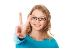 显示胜利标志的愉快的少年 免版税库存照片