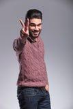 显示胜利标志的愉快的年轻时尚人 免版税库存照片
